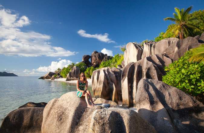 Visitor sitting on rocks on La Digue, Seychelles