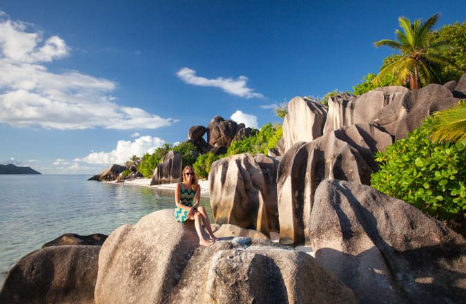 Visitor sitting on rocks on La Digue, Seychelles