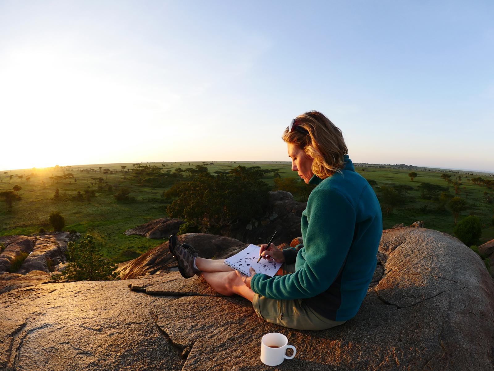 Woman sitting on rock drawing, Serengeti