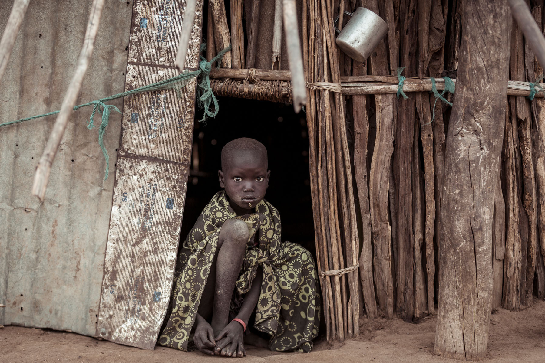 A young Boya girl sits in front of her hut © Joe Buergi