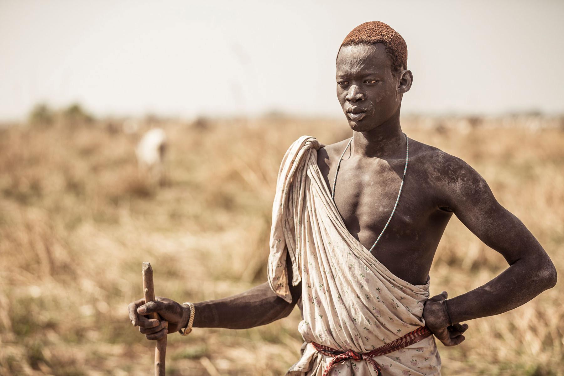 A Mundari man stands guard over his cattle © Joe Buergi