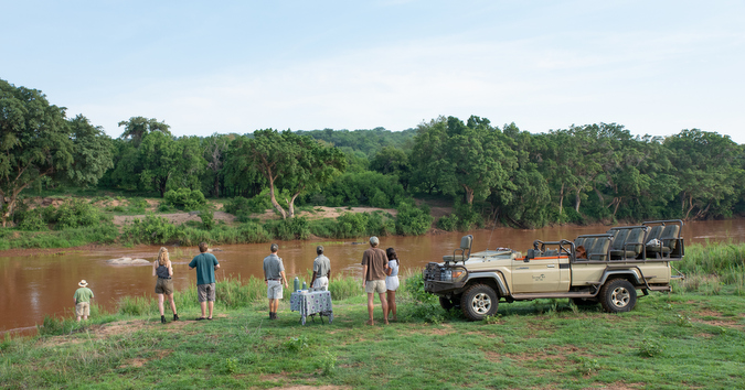 Guests and rangers having drinks by Olifants River
