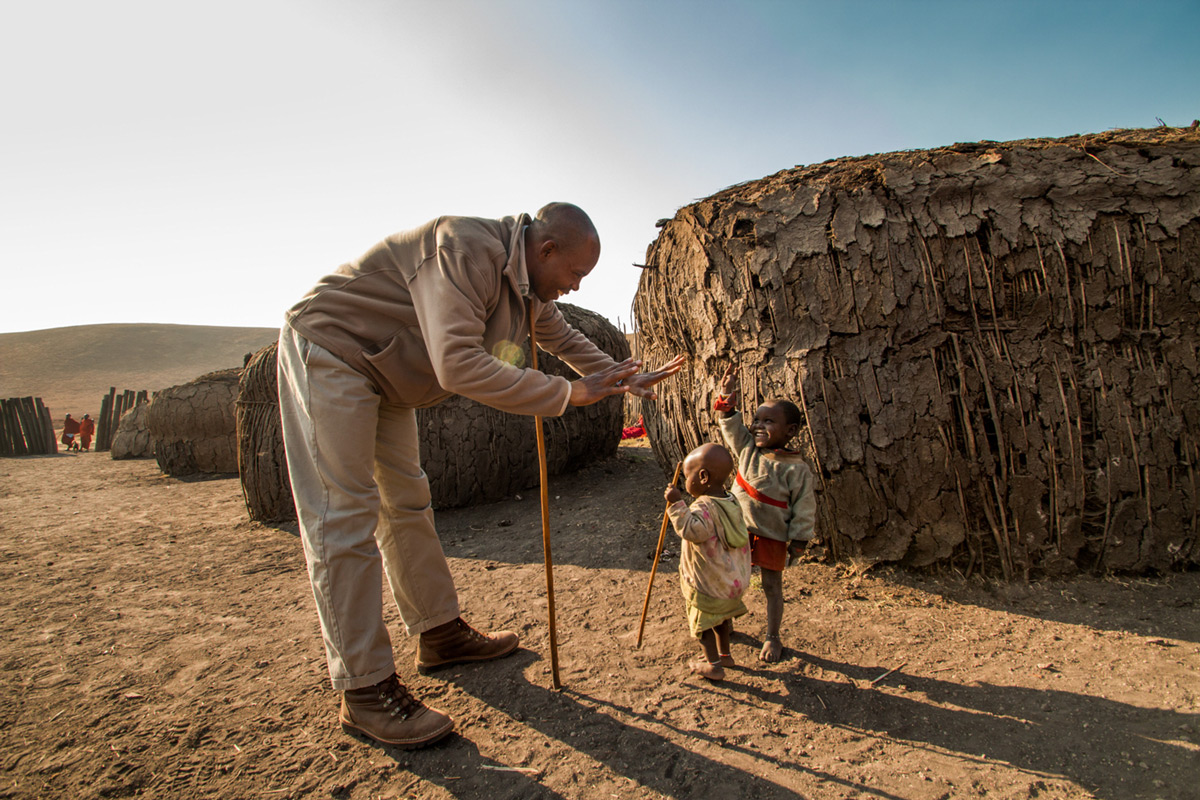 """Future generations"" – reaching out to give children a hand in a Masaai village. Tanzania © Caleb Shepard"