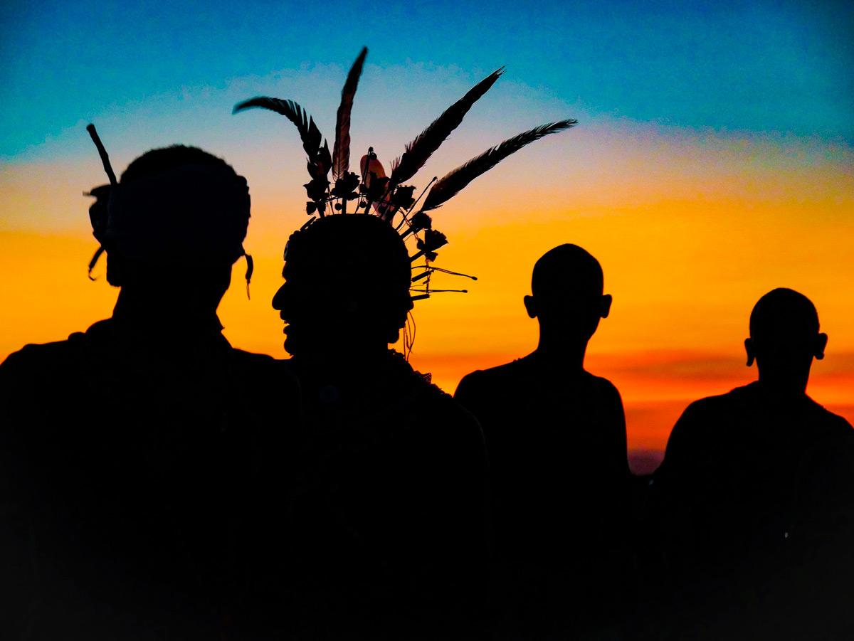 Samburu warriors chat amongst themselves at sunset in Samburu National Park, Kenya © Charlotte Hill