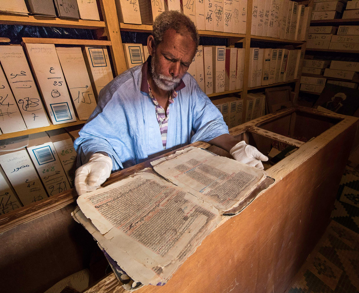 A librarian shows a thousand-year-old Quranic manuscript in an ancient library in Chinguetti, Mauritania © Gary Krosin