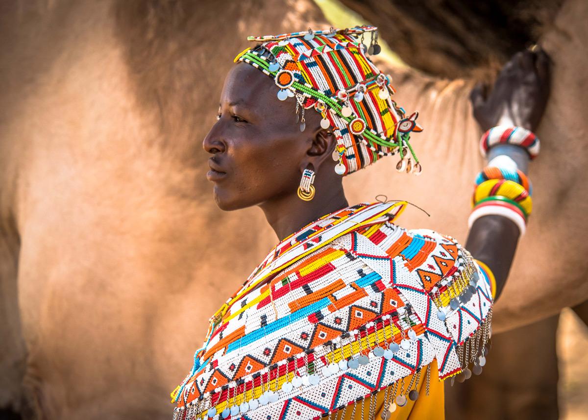 Mpayon, a Samburu woman who is one of nine Mama Tembos who patrol and help protect livestock and wildlife corridors, poses with a camel in Kalama, northern Kenya © Jane Wynyard
