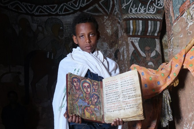 Young boy with a page from the Bible inside Abuna Yemata Guh, Tigray region, Ethiopia © Erika Atienza