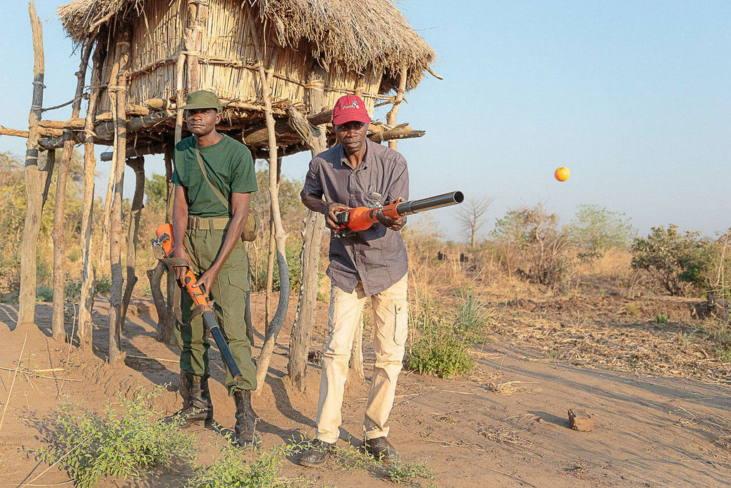 Two men demonstrating the chilli blaster to ward off elephants