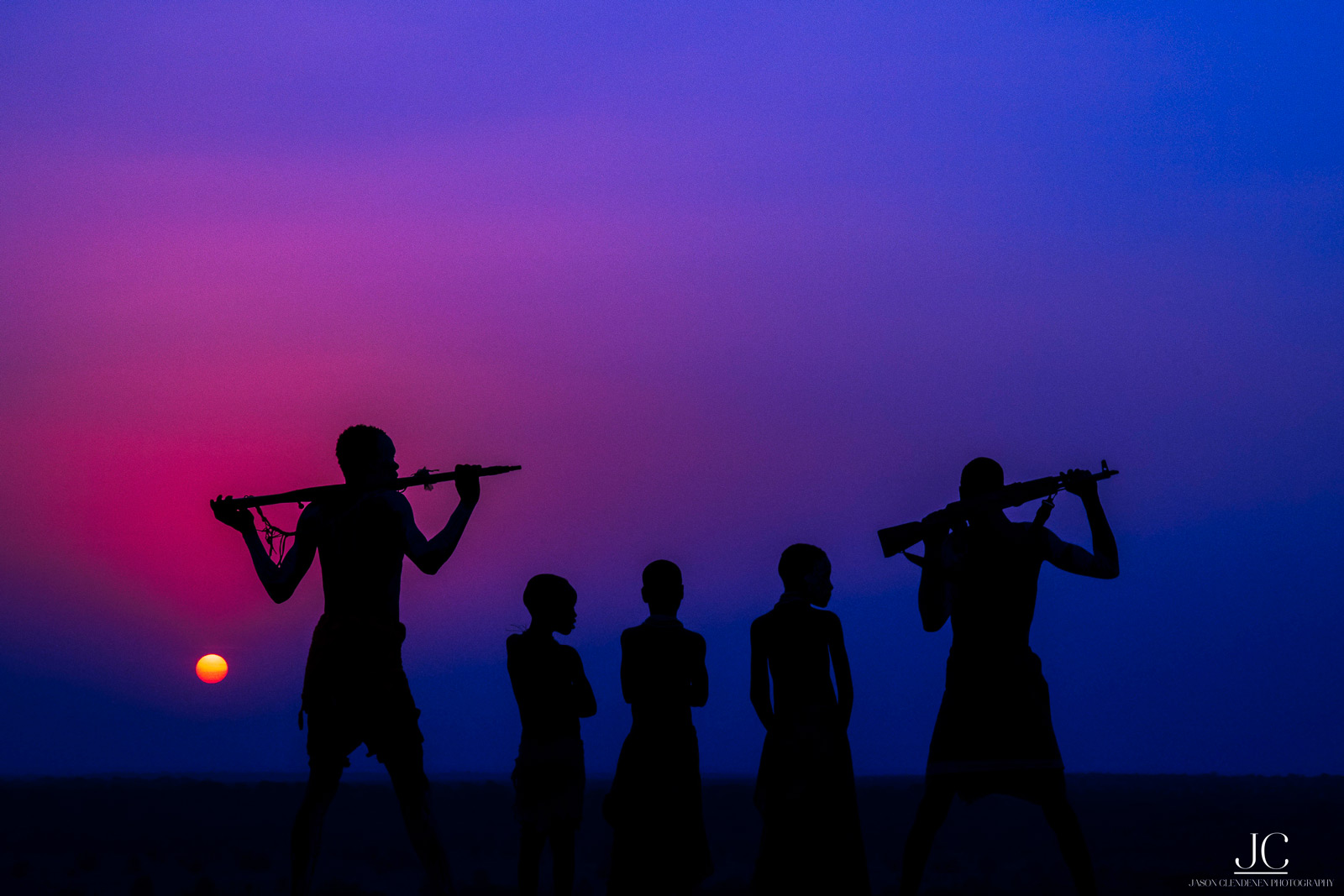Silhouette of Karo tribesmen against the setting sun. Southern Ethiopia © Jason Clendenen