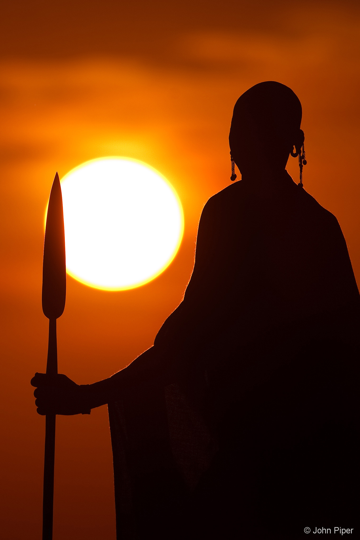 A Maasai tribesman in traditional dress, armed with his spear, looks towards the rising sun. Mara North Conservancy, Kenya © John Piper