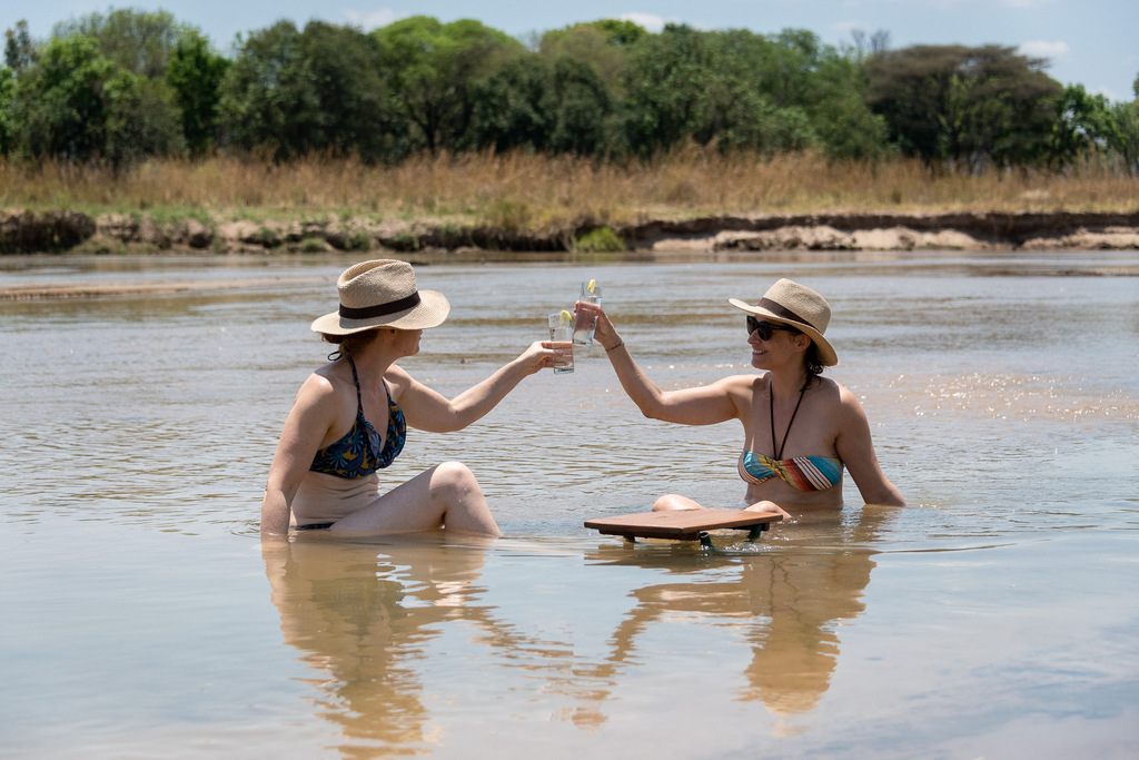Two guests clinking glasses in river in South Luangwa National Park in Zambia